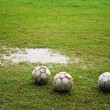 Stock Photo: Footballs on Wet Field