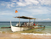 Wooden Outrigger Boat on a Beach Shore — Stock Photo