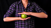 A girl holding a green apple — ストック写真
