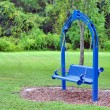 A blue rocking bench in a park. — Stock Photo