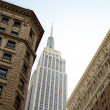 Empire State Building between buildings — Stock Photo
