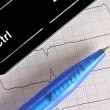 Pen, fragment of keyboard on background of ECG — Stock Photo #22888830