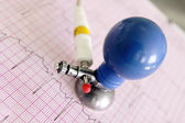 ECG electrode on fragment of electrocardiogram — Stock Photo