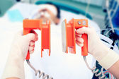 Defibrillator electrodes in hands. Work in the ICU — Stock Photo