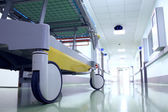 Bed on wheels waiting in the illuminated hospital corridor — Stock Photo
