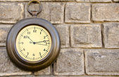 Old street clock on a stone wall — Stock Photo
