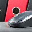 Wireless mouse placed on notebook and three folders in bac — Stock Photo #23540633