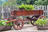 Wooden cart and wicker baskets in the back yard — Stock Photo