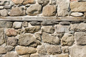 Wall of crushed stone, masonry and wooden plank — Stock Photo