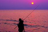 Visser door de zee bij zonsondergang — Stockfoto