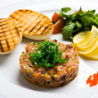 Fish tartare with vegetables and crackers — Stock Photo