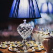 Blue lamp stands on dessert table — Stock Photo
