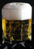 Glass of beer close-up with froth over yellow background — Stock Photo