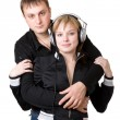 Young happy amorous couple with headphones at home — Stock Photo