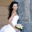 A beautiful bride by the stone wall — Stock Photo
