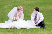 A bride and a groom looking one to another on the grass — Stock Photo