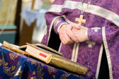 Crossed hands of the praying priest — Stockfoto