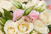 Gold rings and rose bouquet — Stock Photo