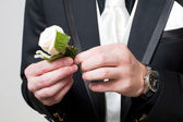A rose in the hands of the man in the suit — Stock Photo