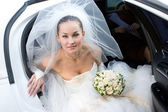 Bride with flowers in the white car — Stock Photo