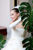 A happy bride near the big leaf of the flower — Stock Photo