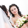 Stock Photo: A beautiful bride looking into the mirror