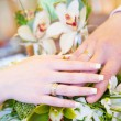 Two hands with wedding rings on the flower bouquet - Stock Photo