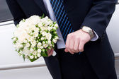A man in suit with watch hands a flower bouquet — Stock Photo