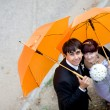 Portrait of bride and groom with orange umbrellas  — Stock Photo
