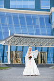 Bride near the modern building — Stock Photo