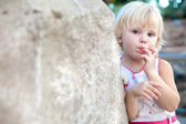 Surprised girl by the stone — Stock Photo
