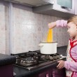 Little girl putting pasta in the pot — Stock Photo #22917406