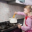 Little girl putting pasta in the pot — Stock Photo #22917408