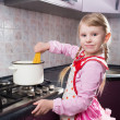 Little girl putting pasta in the pot — Stock Photo #22917414