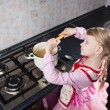 Little girl putting pasta in the pot — Stock Photo