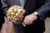 Man with watch hands a flower bouquet — Stock Photo