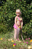 Little girl with hosepipe — Stock Photo