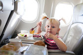 Girl eating in the airplane — Stock Photo