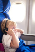Child with headphones in the plane — Stock Photo
