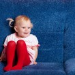 Happy small girl on the sofa — Stock Photo