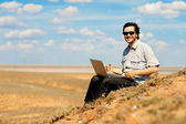 Happy man with laptop outdoors — Stock Photo
