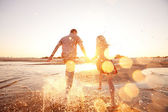Couple running on the beach — Stock fotografie
