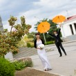 Bride and groom with orange umbrellas — Stock Photo