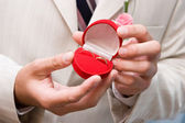 Box with golden rings in hands — Stock Photo