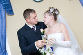 Bride and groom with glasses of champagne — Stock Photo