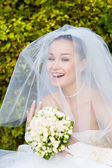 A portrait of the beautiful happy bride under the veil — Stock Photo
