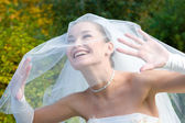 A smiling bride looks through the veil — Stock Photo