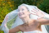 Uma noiva sorridente parece através do véu — Foto Stock