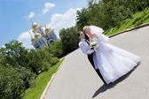 šťastnou nevěstu a ženicha u kostela — Stock fotografie