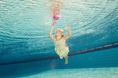 Swimming under the water girl with flower — Stok fotoğraf